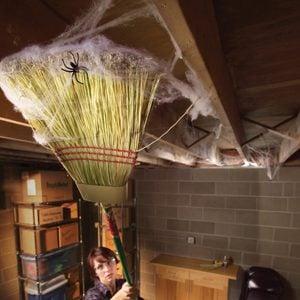woman sweeps away cobwebs in a basement