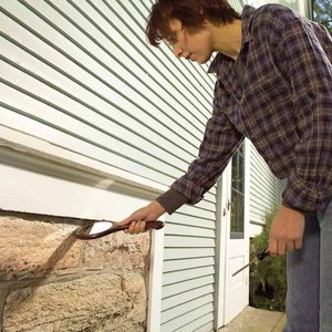 Woman-checks-for-openings-in-the-siding-of-a-house