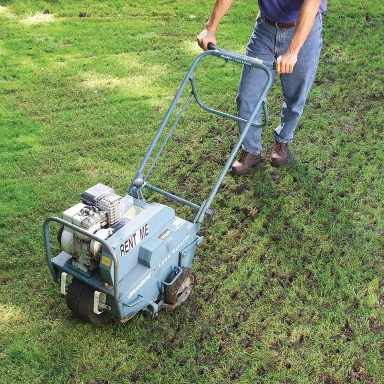 Man-walks-behind-lawn-aerator
