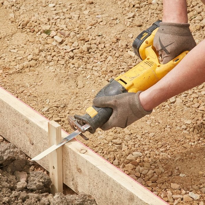 Chopping the top of form stakes off for easier screeding | Construction Pro Tips