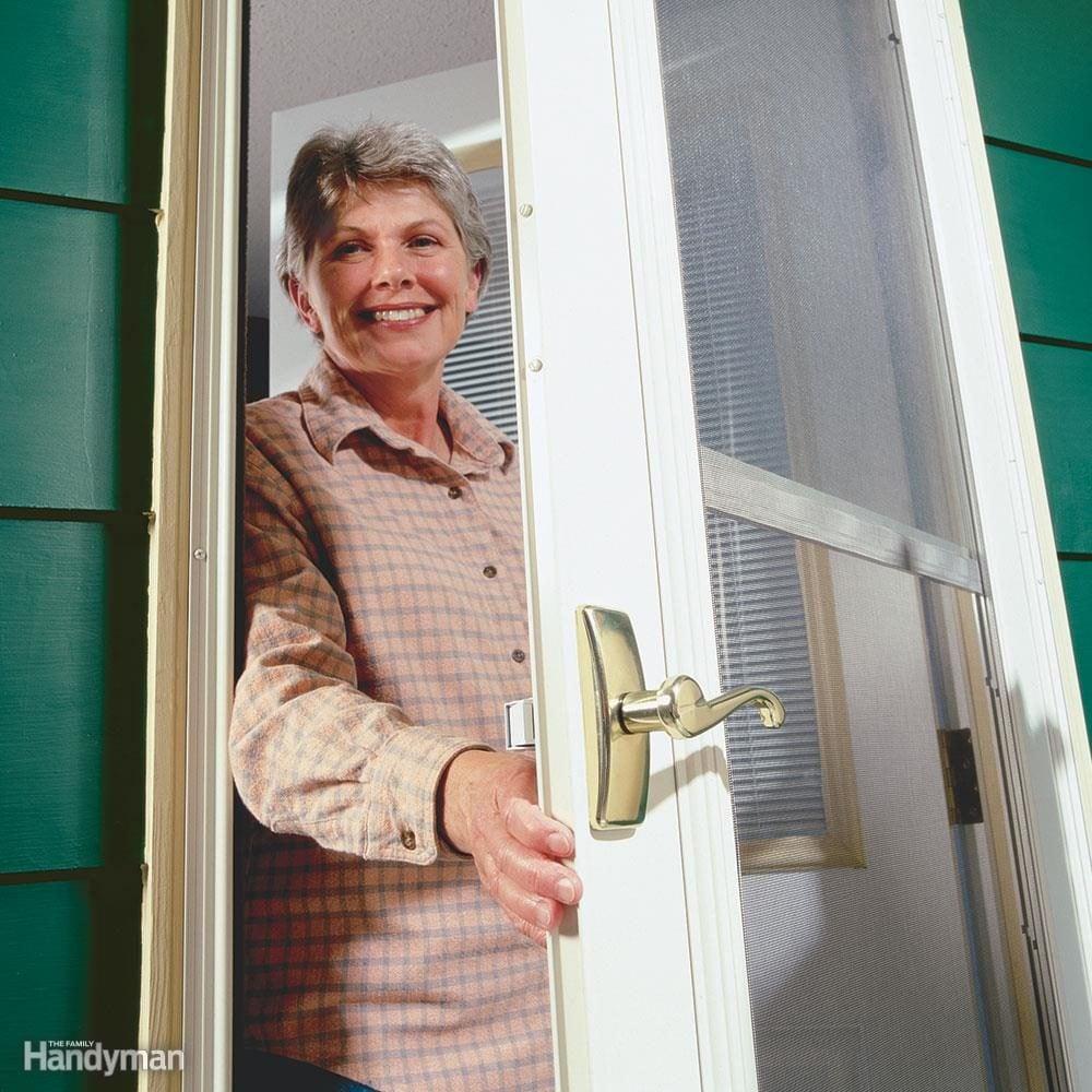 woman smiles as she opens storm door