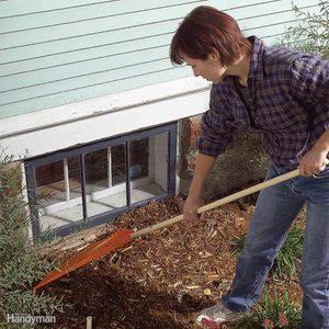 Woman rakes mulch away from egress window