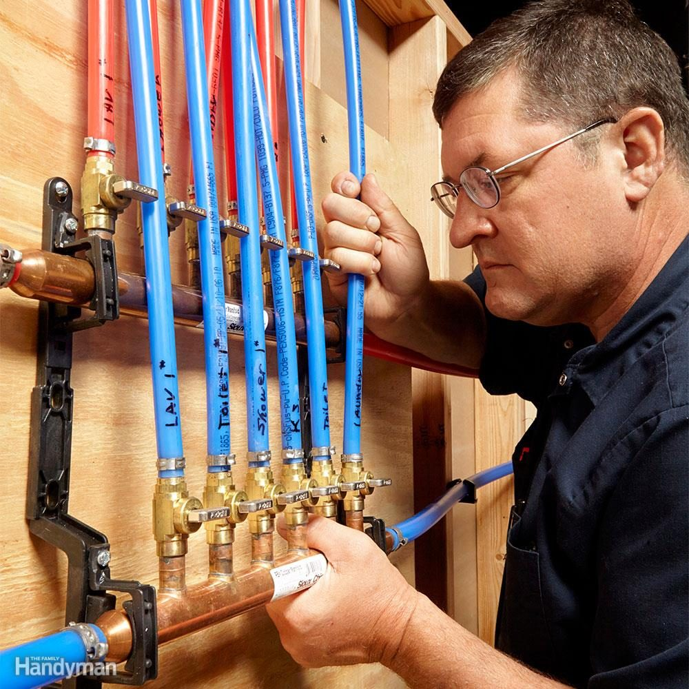 Man inspects PEX pipe lines