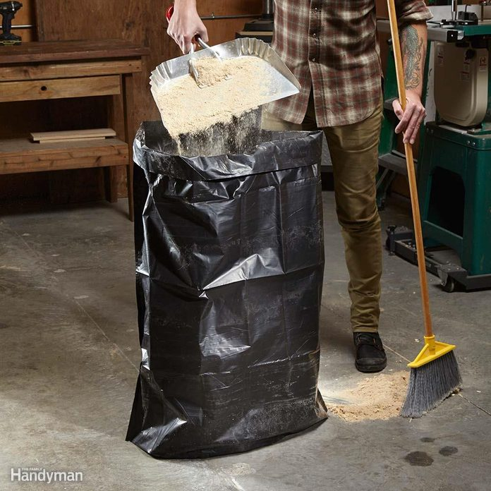 man empties a dust bin into a stand-up garbage back