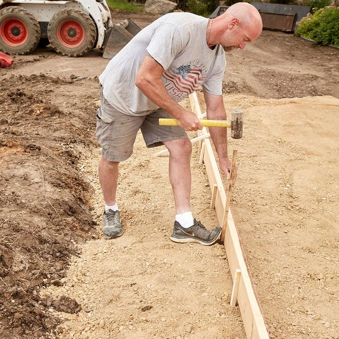 Pounding form stakes into the ground | Construction Pro Tips