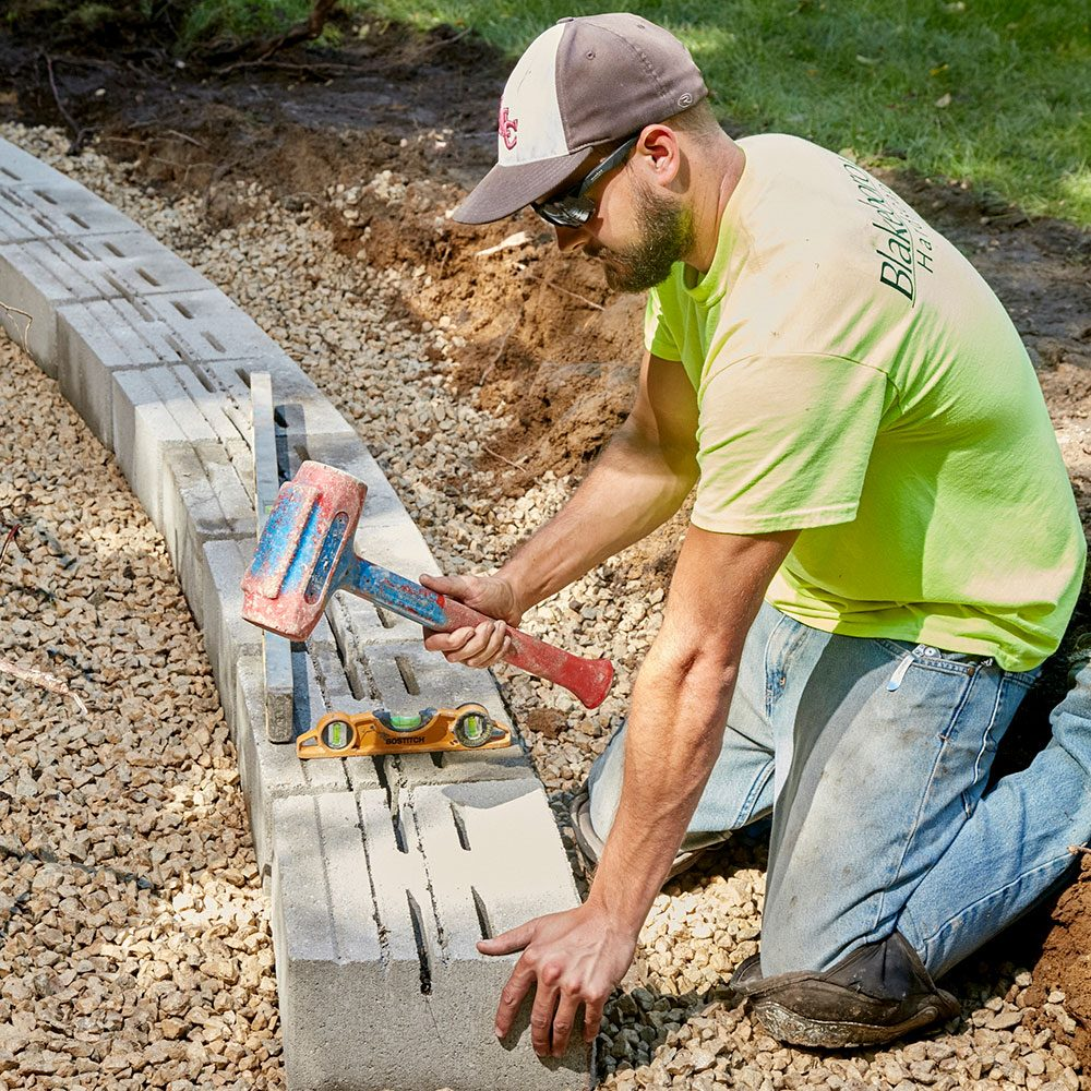 Creating a level block base for a stone retaining wall | Construction Pro Tips