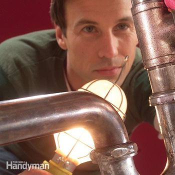 man shines light on under sink pipes
