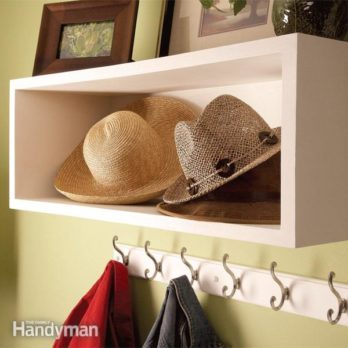 hats sit in a simple box shelf above coat hangers