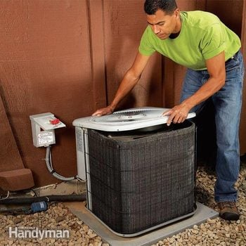 man removes the lid of an air conditioner