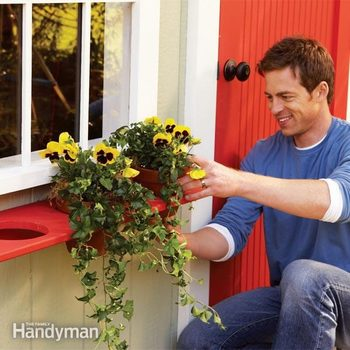 man inspects plants hanging in a wooden planter box