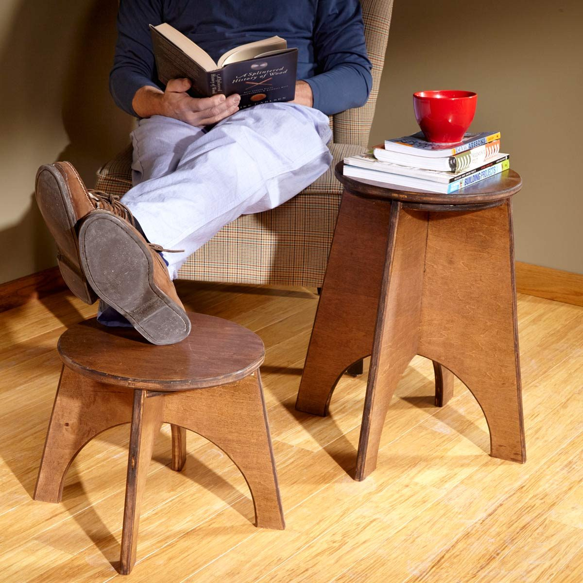 man reading and resting legs on handmade stool