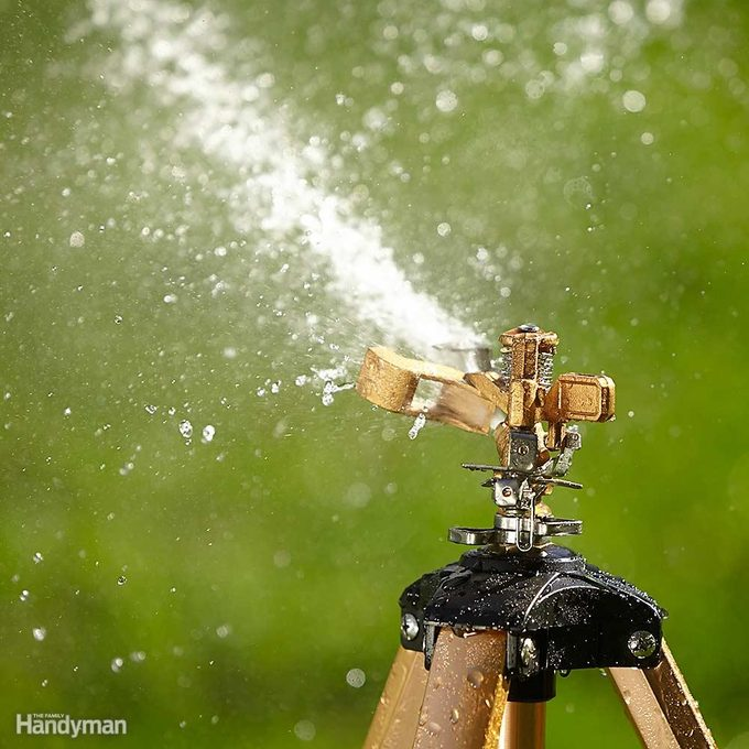 pulsating sprinkler sprays water on lawn