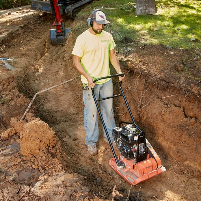 Compacting the dirt in the bottom of a trench   Construction Pro Tips
