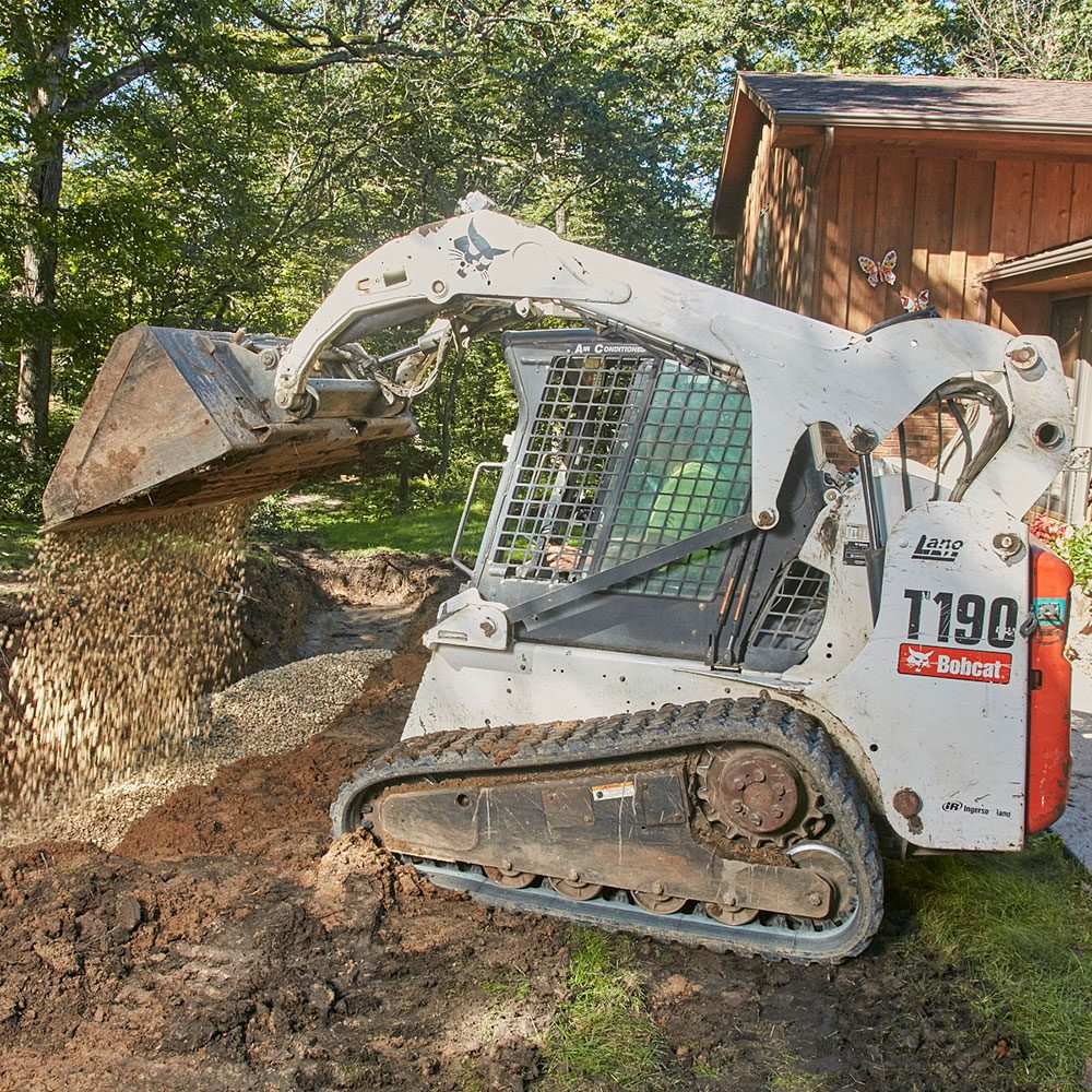 Laying a rock base with a Bobcat | Construction Pro Tips