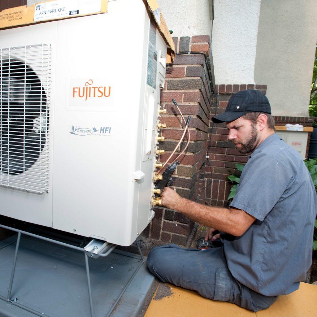 Man installing a mini-split | Construction Pro Tips
