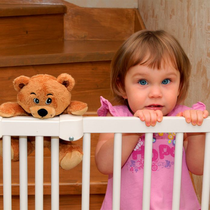 little girl with bear behind child lock