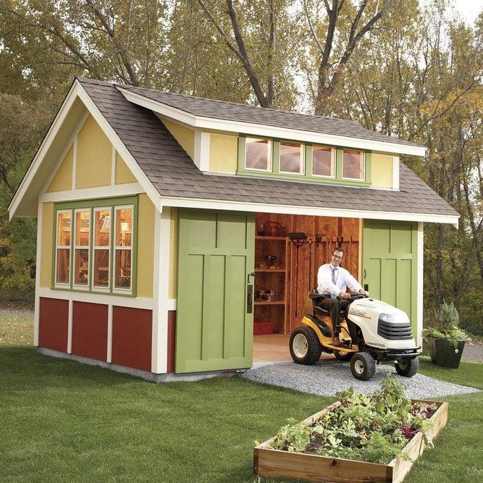 DIY garden shed backyard idea man driving tractor out of garden shed