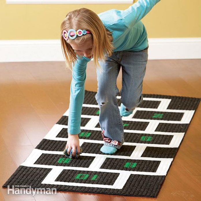 girl playing hop scotch game inside