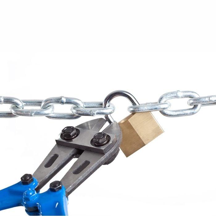 A bolt cutter snipping a padlock | Construction Pro Tips