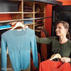woman organizing closet holding up a sweater on a hanger clothes