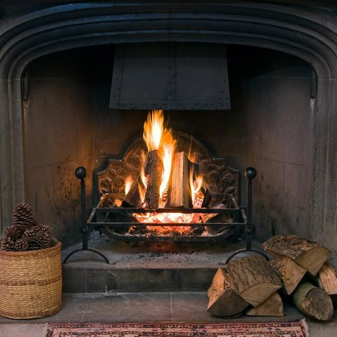 fire within a large stone arched fireplace, with pile of logs and basket of pine kernels fireplace fire