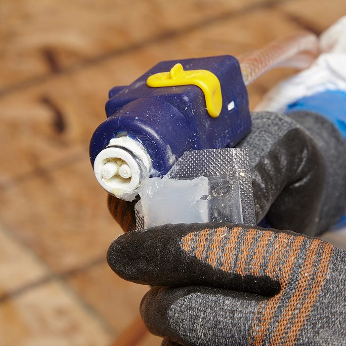 Lubing the tip of a spray foam gun | Construction Pro Tips