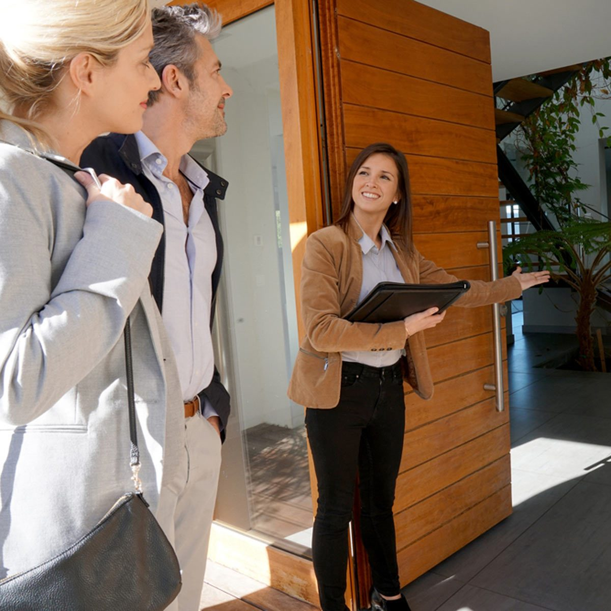shutterstock_580640611 Real estate agent inviting couple to enter house for visit home inspection
