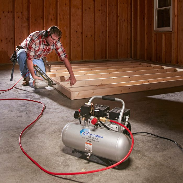 Building framing with a nailer connected to a compressor   Construction Pro Tips