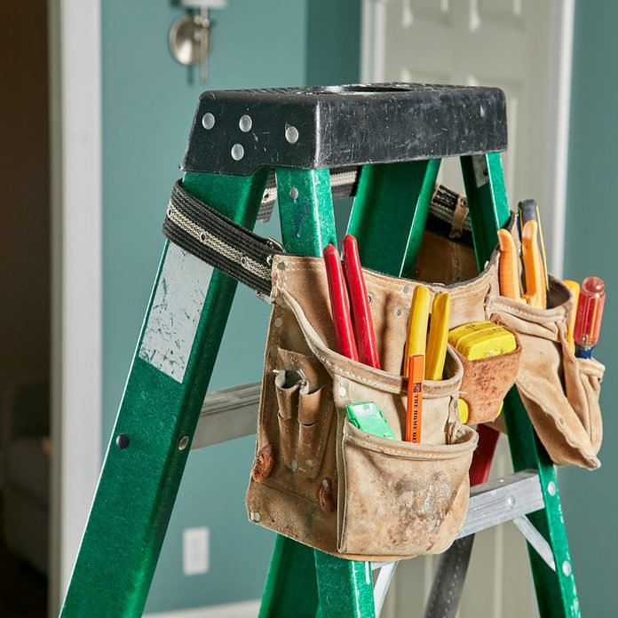 Tool bag draped over a ladder for easy access | Construction Pro Tips