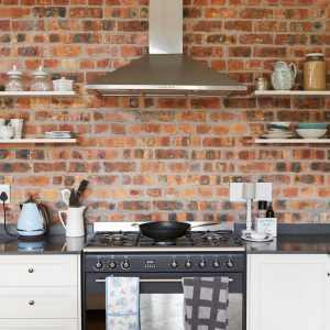 brick wall in kitchen with open shelves