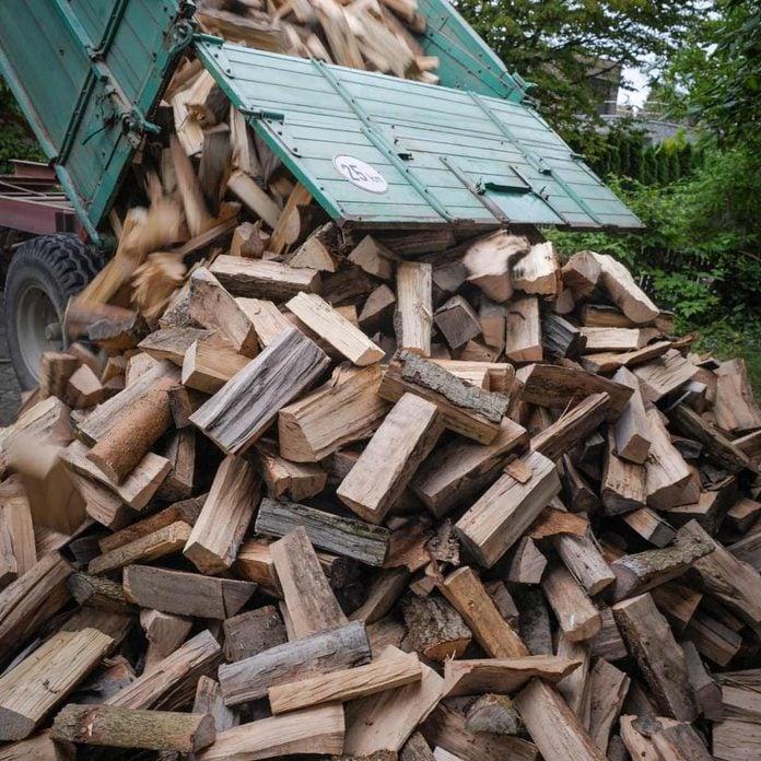 shutterstock_586547087 truck dumping firewood logs