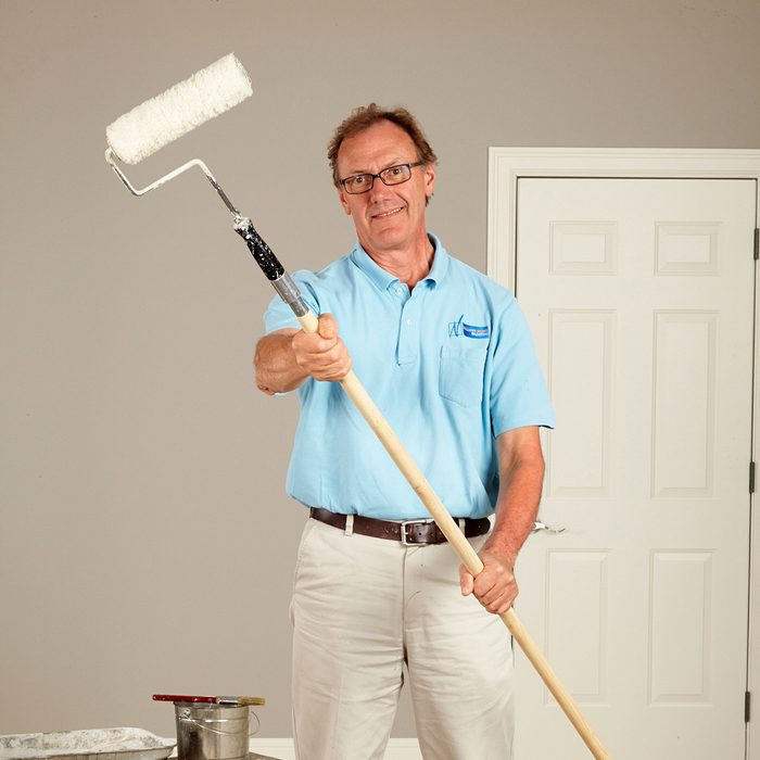 Man holding a painting pole   Construction Pro Tips