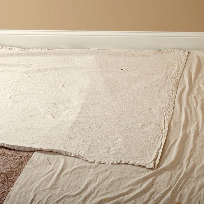 Laying down narrow drop cloths next the walls   Construction Pro Tips