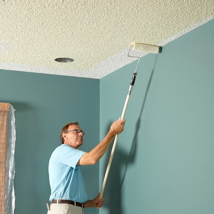 Man rolling darker paint onto a textured ceiling | Construction Pro Tips