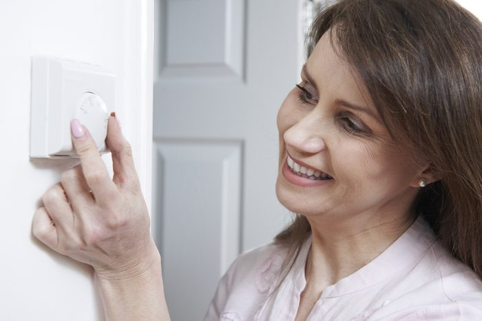 Woman adjusting thermostat.
