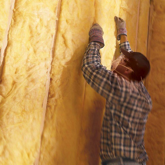 man installs fiberglass insulation
