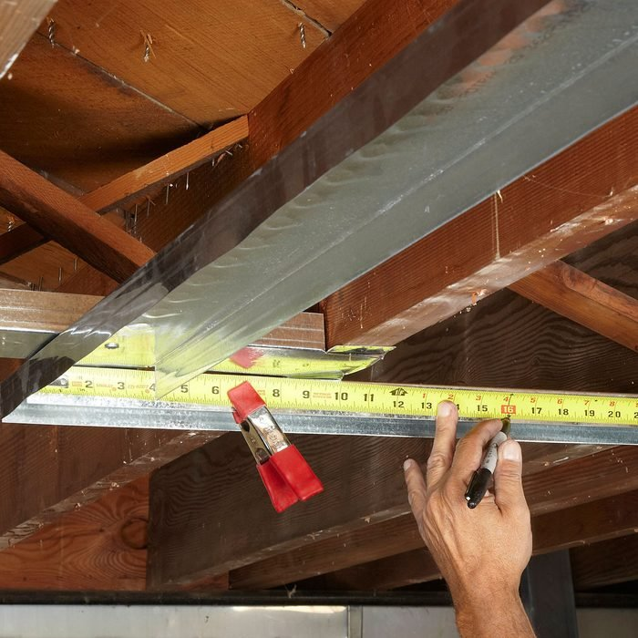 Lay out studs with a tape measure and a clamp | Construction Pro Tips