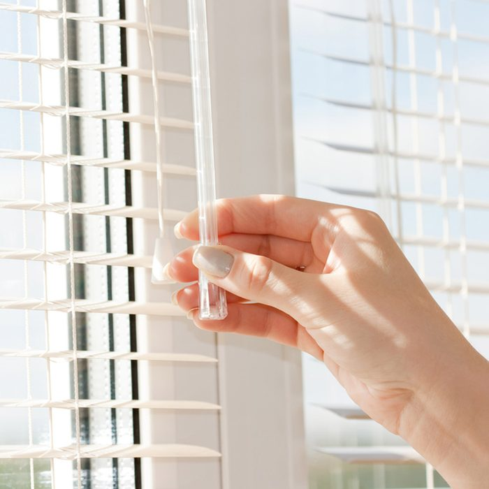 hand adjusting the blinds on a window