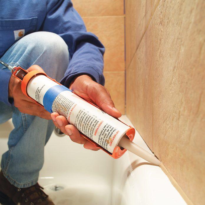 Caulking the tile seam in a bathtub | Construction Pro Tips
