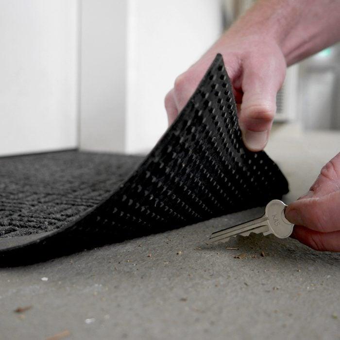 hands retrieving a hidden key from under a mat