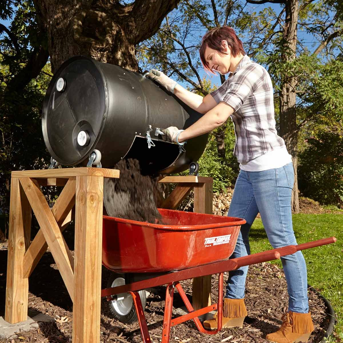 DIY compost bin made from a 55 gallon drum. Elevated legs make it easy to fill a wheelbarrow with compost.