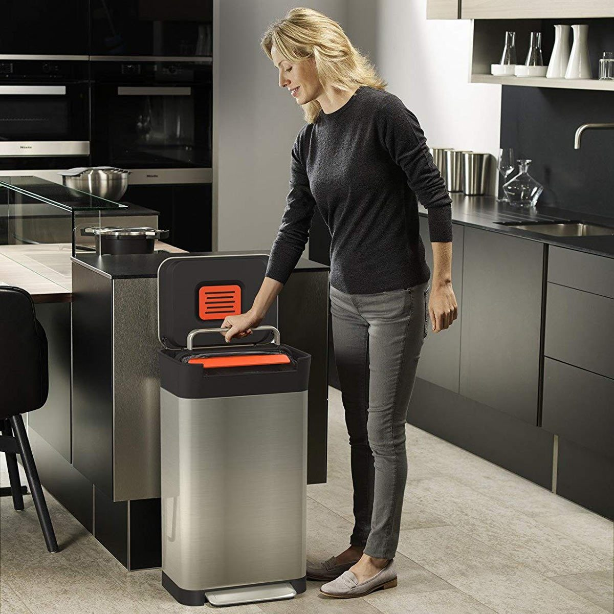woman-activates-kitchen-trash-compactor