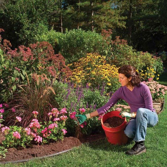 woman adding mulch to garden