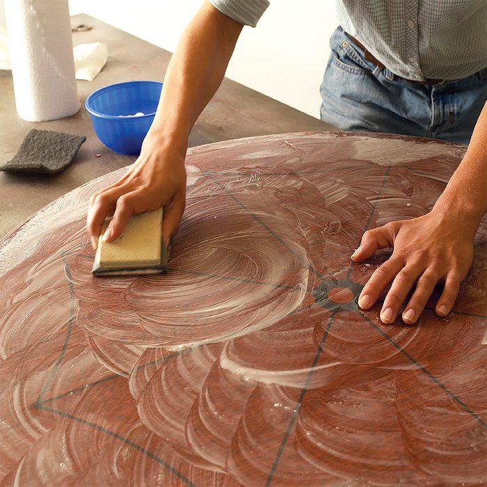 Man sanding table top with sand paper and soapy water   Construction Pro Tips