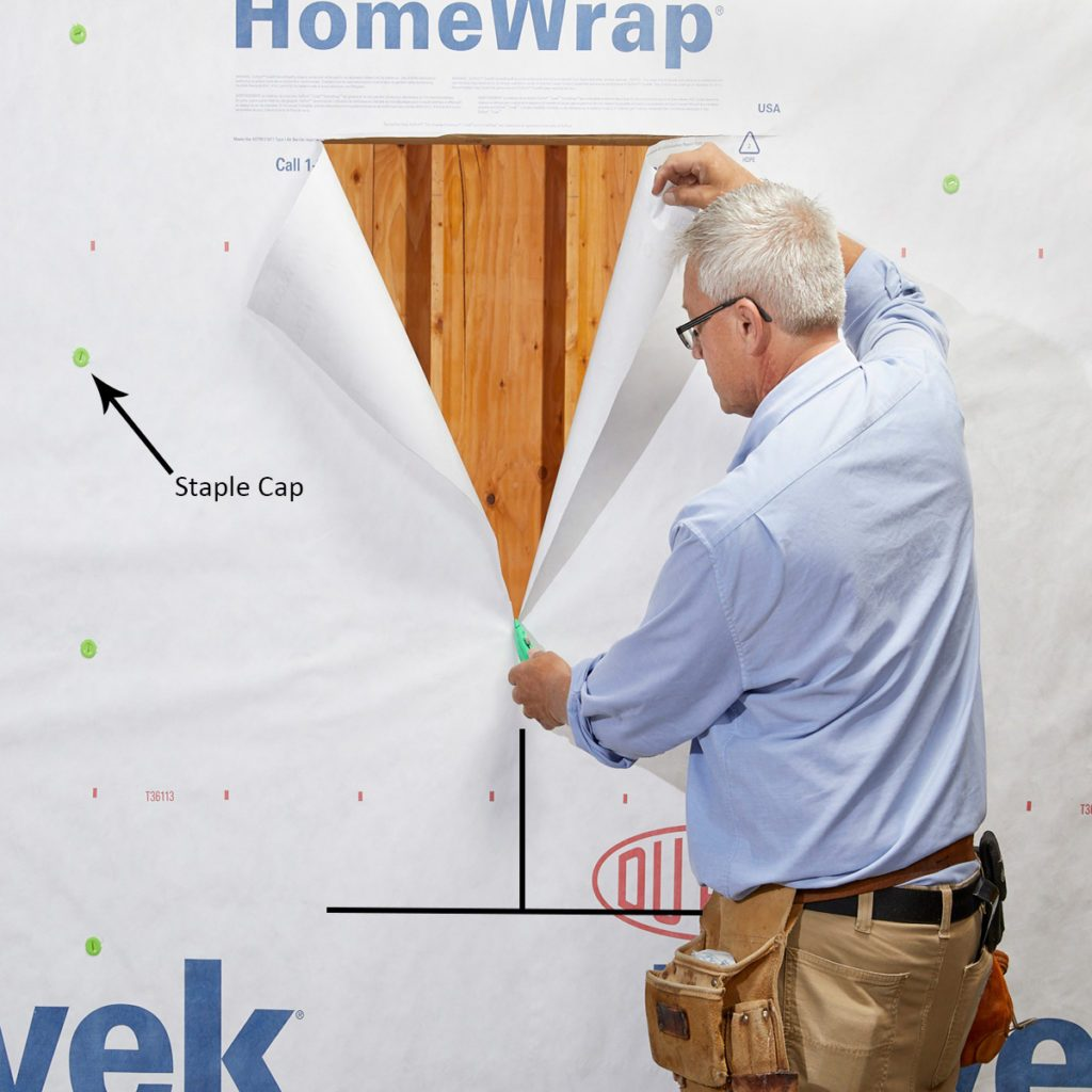 Man cutting a hole in the Tyvek | Construction Pro Tips