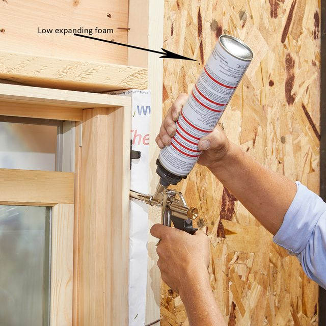 Using low-expanding foam to foam up the sides of a window | Construction Pro Tips