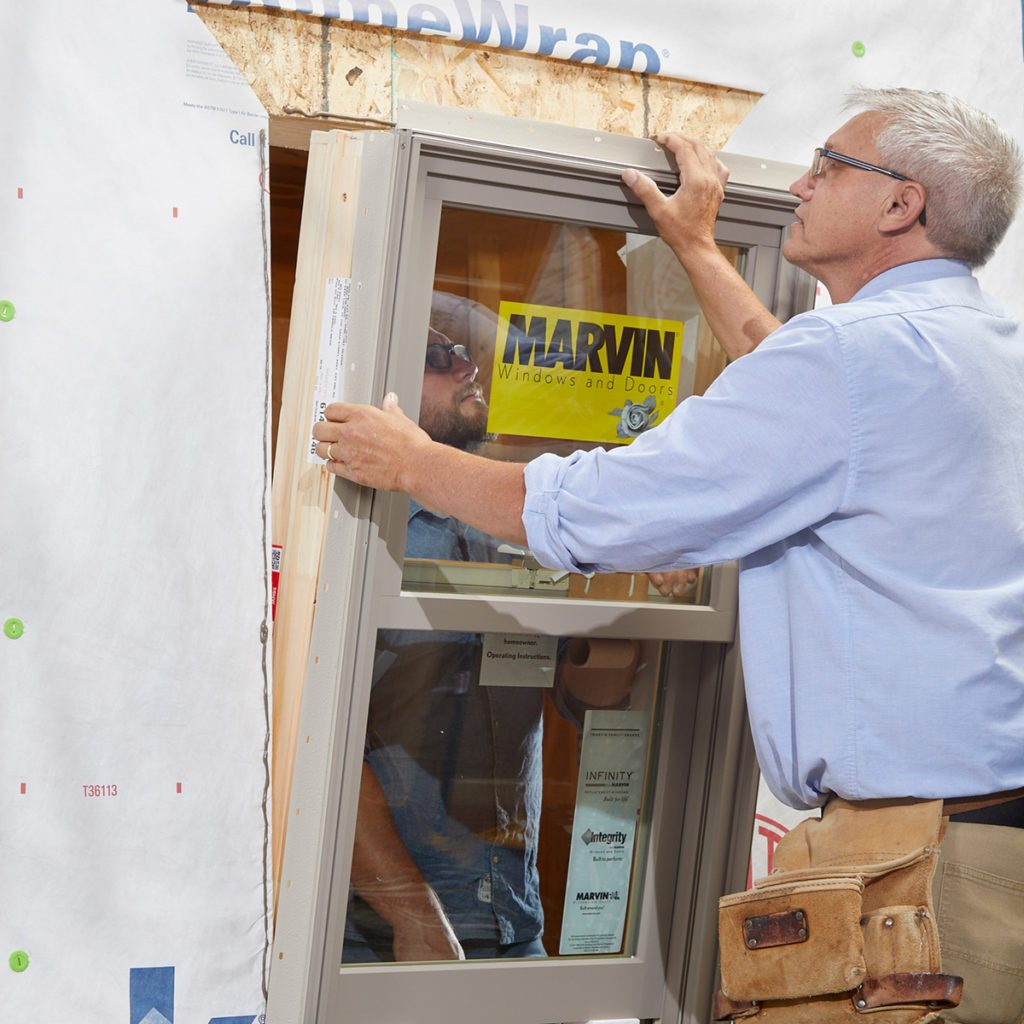 Two men placing a window into place | Construction Pro Tips