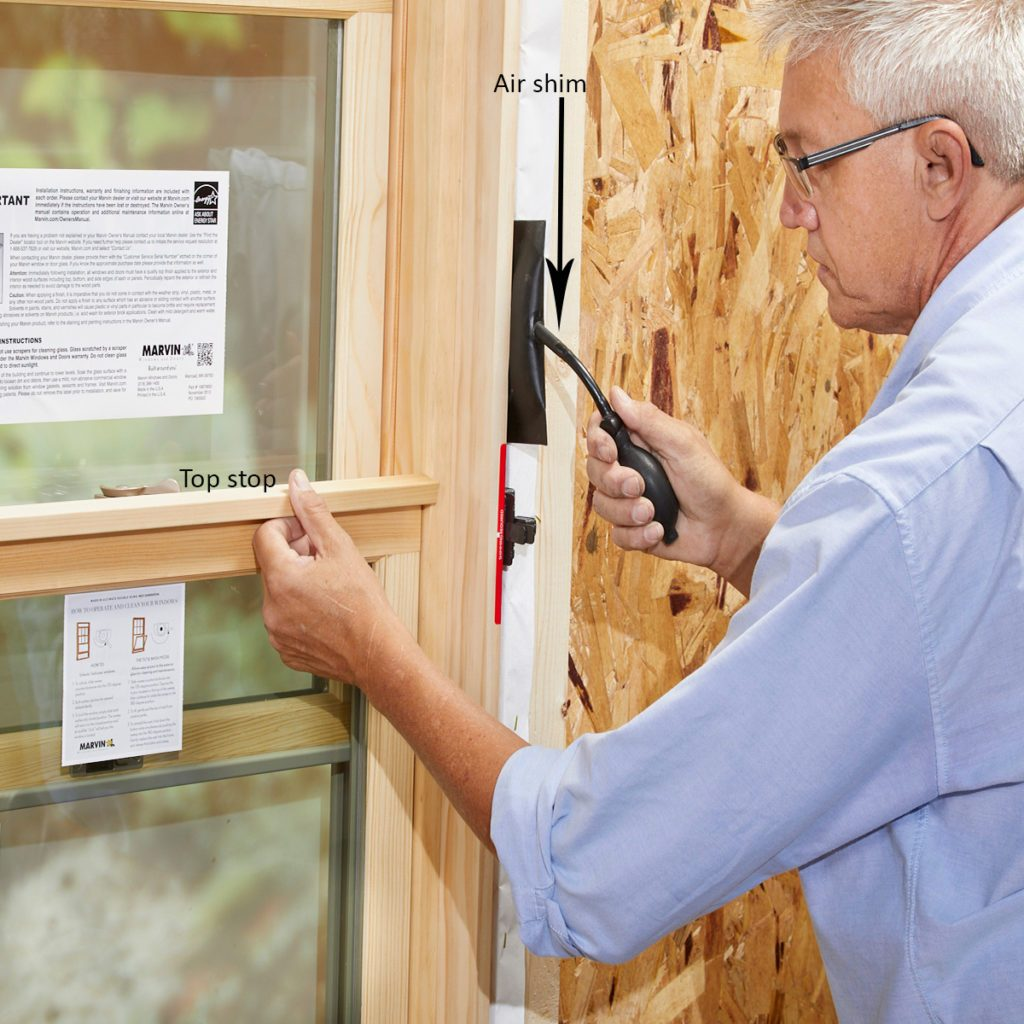 Man using an air shim to install a window | Construction Pro Tips