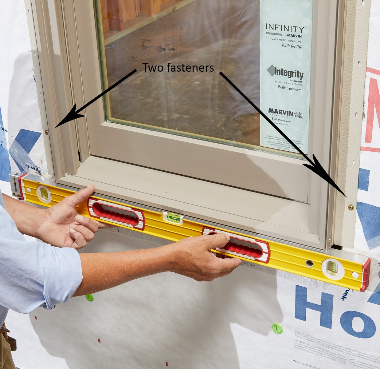 Man leveling and fastening the bottom of a window | Construction Pro Tips