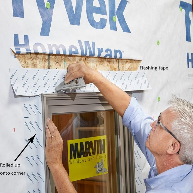 Man taping the flanges of a window down during install | Construction Pro Tips